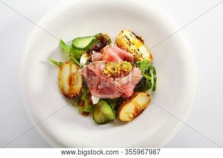 Salad with roast beef and vegetables. Delicious meat with cut potatoes and cucumbers in white plate. Tasty restaurant dish with seasonings and fresh greenery. Food presentation, haute cuisine