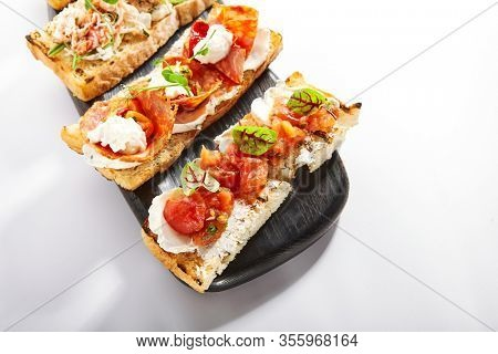 Bruschetta with baked tomatoes closeup view. Aromatic snacks with cheese and vegetables. Traditional antipasto, starter dish. Italian cuisine, served crunchy appetizers with greenery