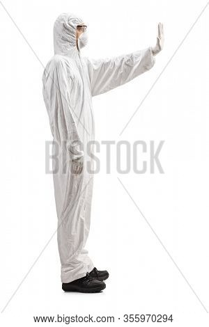 Full length profile shot of a man in a white decontamination suit gesturing stop isolated on white background