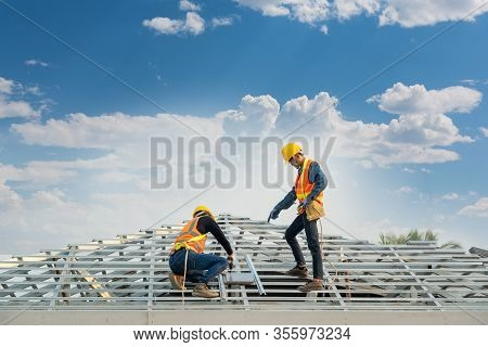 Roofer Worker In Special Protective Work Wear And Gloves,using Pneumatic Gun And Installing Concrete
