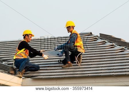 Construction Worker Wearing Safety Harness Belt During Working Installing Concrete Roof Tile On Top