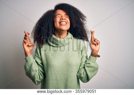 Young beautiful african american woman with afro hair wearing green winter sweater gesturing finger crossed smiling with hope and eyes closed. Luck and superstitious concept.