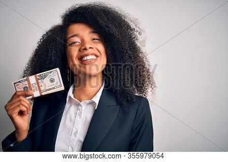 Young african american business woman with afro hair holding a bunch of cash dollars banknotes with a happy face standing and smiling with a confident smile showing teeth
