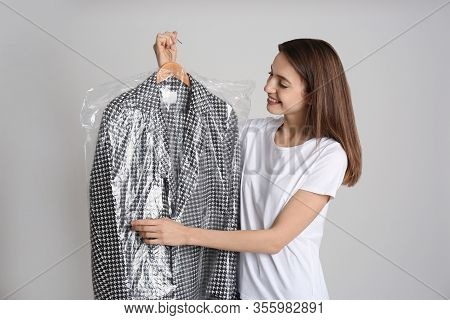 Young Woman Holding Hanger With Jacket In Plastic Bag On Grey Background. Dry-cleaning Service