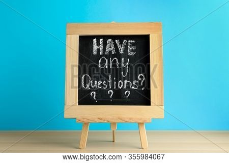 Blackboard With Phrase Have Any Questions On Wooden Table Against Blue Background