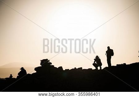 Silhouettes Of Hikers On A Rocky Hilltop In The Atacama Desert, Chile.