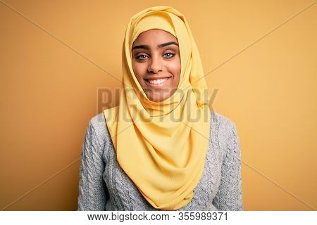 Young beautiful african american girl wearing muslim hijab over isolated yellow background with a happy and cool smile on face. Lucky person.