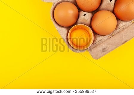 Egg Chicken Eggs. Top View Of An Open Gray Box With Brown Eggs Isolated On A Yellow Background. One