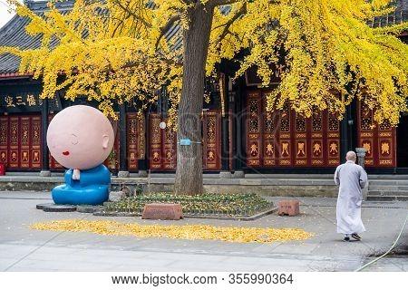Chengdu, Sichuan Province, China - Dec 1 2019 : Manga Monk Statue And Monk In Daci Buddhist Temple W