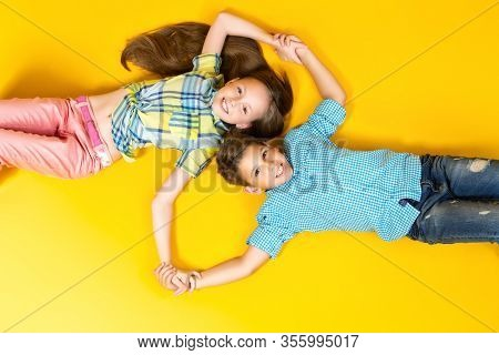 A portrait of two cheerful young kids over the yellow background. Summer casual kids fashion.