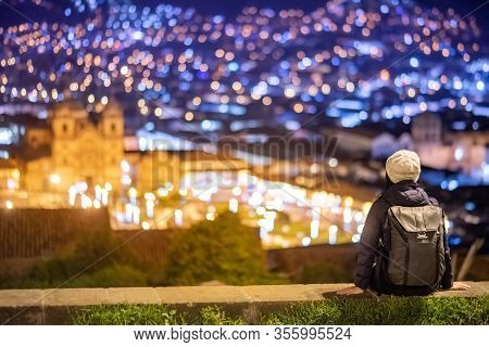 Asian Woman Traveler Sitting On Viewpoint Looking At Illuminated Cusco City At Night. Cusco (cuzco)
