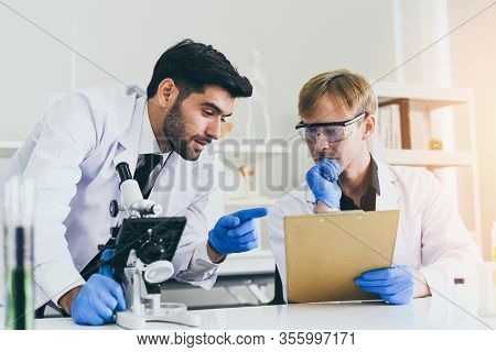 Team Of Scientist Research Working Together Conduct Experiments And Looks On Microscope In Modern La