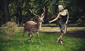 Young blonde lady running with deer poster