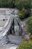 This photograph shows a section of the 35W bridge in Minneapolis Minnesota which collapsed under its own weight on August 1 2007. The bridge deck is wrapped around a bridge support. poster