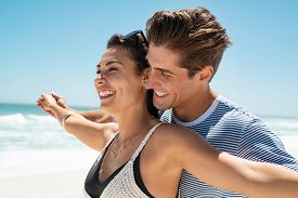 Romantic couple with outstretched arms enjoying summer vacation. Cheerful husband and beautiful wife during honeymoon at sea. Happy smiling young couple with outstretched arms at beach.