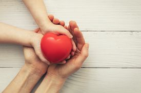 Red Heart In Child And Mother Hands On White Wooden Background. Concept Of Love, Charity, Empathy
