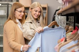 Happy young woman showing her mother white sweatshirt while both shopping in boutique or clothing department in the mall