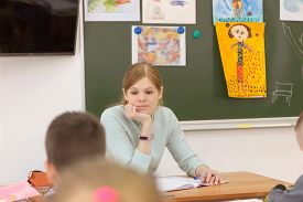 Young Beautiful Teacher Thinking Of Something In Class. Red Haired Woman Sittin Near The Blackboard.