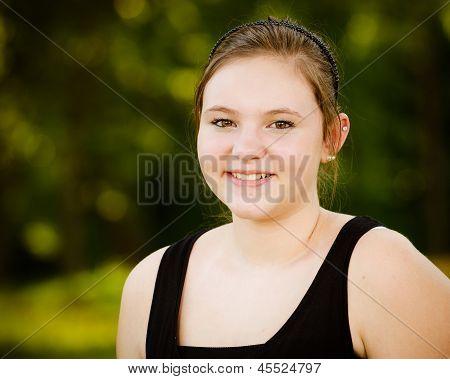 Portrait of happy teenage or adolescent girl outdoors