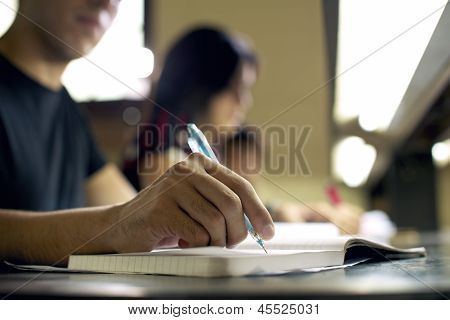 Young Man Doing Homework And Studying In College Library