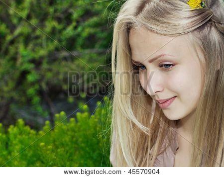 Beautiful woman on a green summer meadow