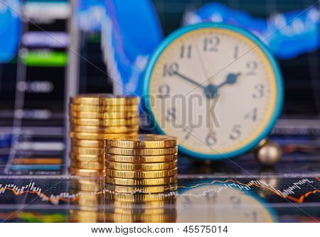 Downtrend Stacks Of Golden Coins, Clock And The Financial Chart As Background. Selective Focus