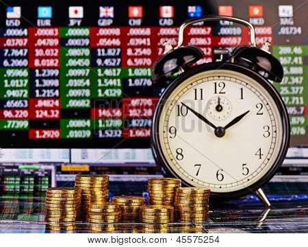 Stacks Of Golden Coins, Clock On The Right And The Financial Chart As Background. Selective Focus
