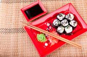 Vegetarian sushi roll served in a form of flower on a red plate on a bamboo mat poster
