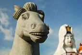 smiling stone horse with goddess of merci statue in background poster