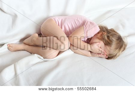 Worried crying child lying on a bed.