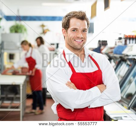 Portrait of confident male butcher standing arms crossed at store with colleagues working in background