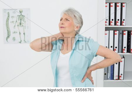 Senior woman suffering from neck pain standing in the medical office