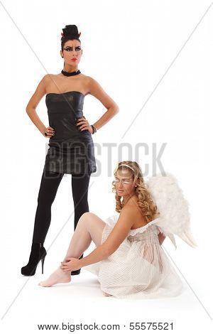 Devil standing confident, angel sitting on floor.