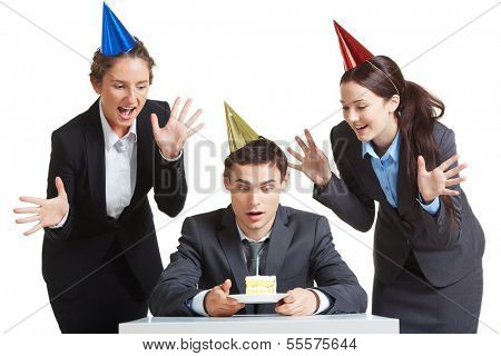Portrait of young businessman in birthday cap looking at piece of cake with two joyful females near by