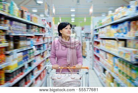 Woman Pushing Shopping Cart Looking At Goods In Supermarket