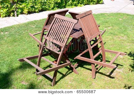 four wooden chairs and a table in nature