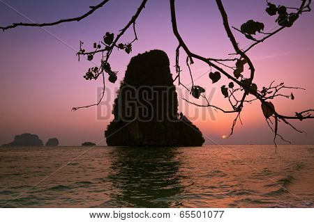 Sunset At Tropical Beach Landscape With Tree. Rock Formation Island Silhouette Under Evening Sun At