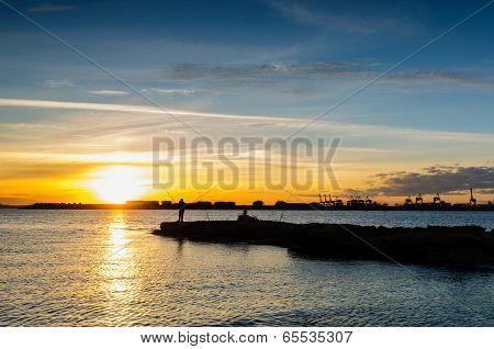 Sunset And Fishing Man