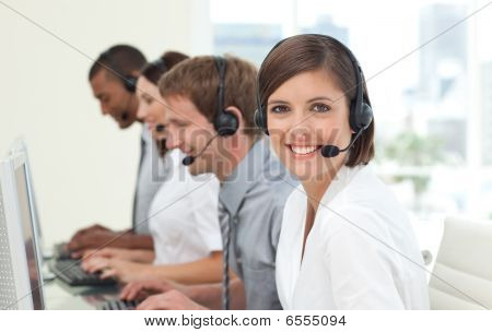 Customer service agents with headset on in a call center poster