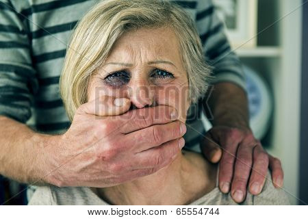 Portrait of woman victim of domestic violence. Man abusing senior woman with black eye- poster