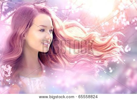 Fantasy Girl with long pink blowing hair. Spring or summer beauty teen girl with flowers. Fashion Art Beauty Portrait. Beautiful Girl in Fantasy Magical Spring Garden