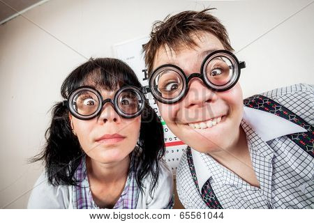 Two funny person wearing spectacles in an office at the doctor