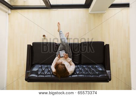 Young Woman Sitting On A Sofa With Digital Tablet Surfing Online