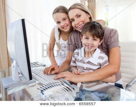 Fürsorgliche Mutter und ihre Kinder am Computer