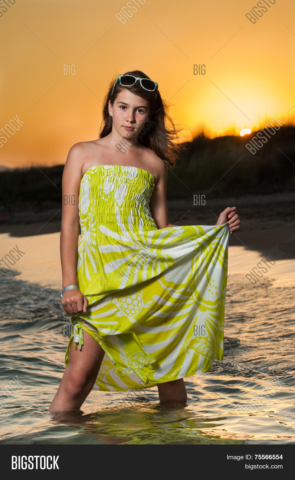2fd8082bd98 Beautiful young brunette girl with yellow dress posing on the beach during  sunset. Cute teen