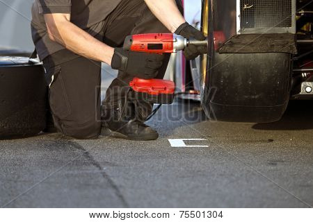 Race car being serviced with new slick tires by a mechanic during a race in the pit lane