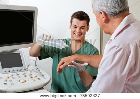 Young male radiologic technician smiling while putting gel to male patient's hand poster