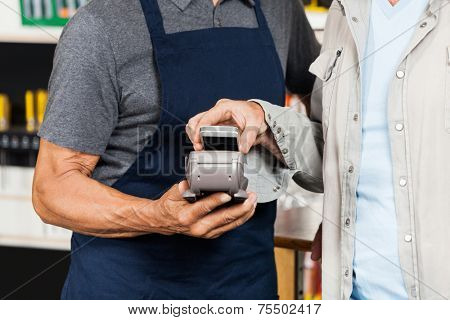 Male customer paying with mobilephone using NFC technology in hardware store