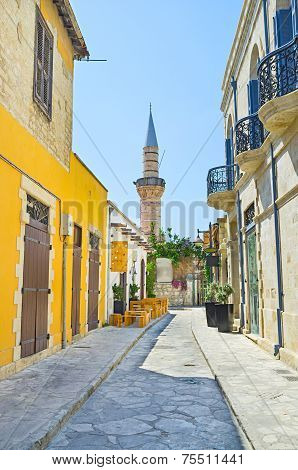 The narrow street with the small outdoor cafe and minaret of the Grand Mosque Cami Kebir on the background Limassol Cyprus. poster
