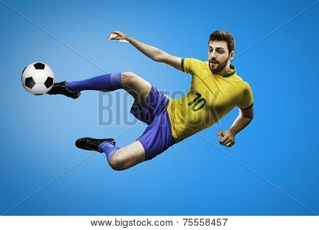 Brazilian soccer player in the jump kicks the ball on blue background